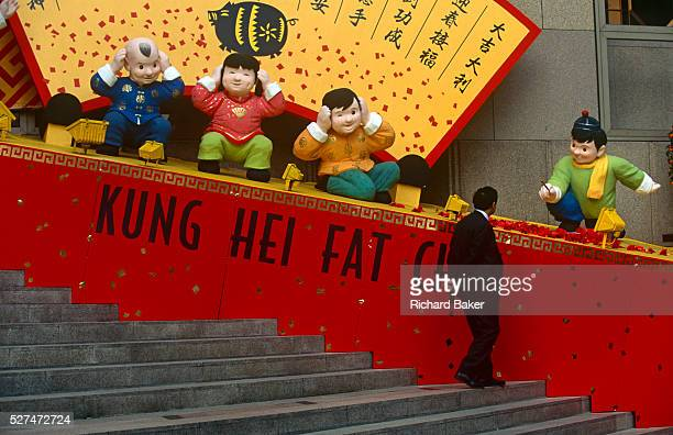 The Chinese words Kung Hei Fat Choi or Happy New Year with cartoon characters outside Bank of China building Hong Kong A local businessman stops to...