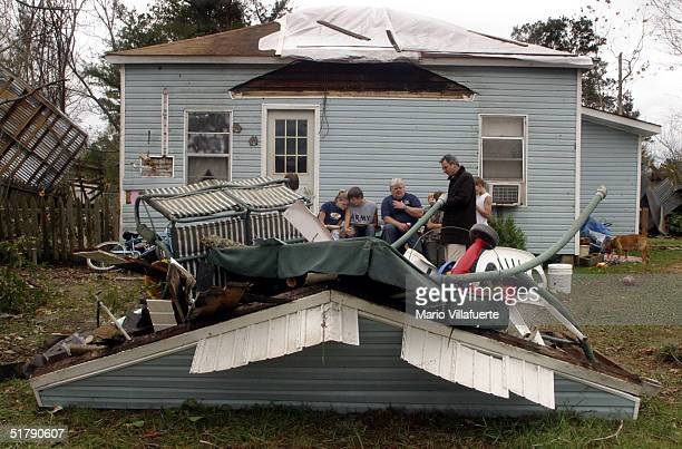 The Chisolm family sits on the front porch of their damaged home on November 24, 2004 in Olla, Louisiana. Tornados swept across central Louisiana...