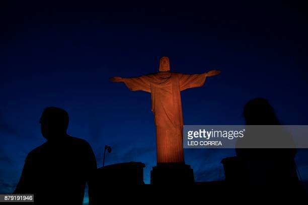The Christ the Redeemer statue is lit up with orange lights during the International Day for the Elimination of Violence Against Women in Rio de...