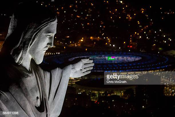 The Christ the Redeemer statue is seen at sunset in front of the Maracana Stadium ahead of the 2016 Summer Olympic Games on July 31 2016 in Rio de...