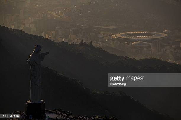 The Christ the Redeemer statue left and the Maracana Stadium a 2016 Summer Olympics venue right are seen in this aerial photograph taken above Rio de...