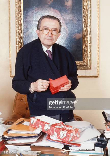 The Christian Democracy party senator Giulio Andreotti is standing behind his desk of his office with a Christmas present in his hands Italy 1988