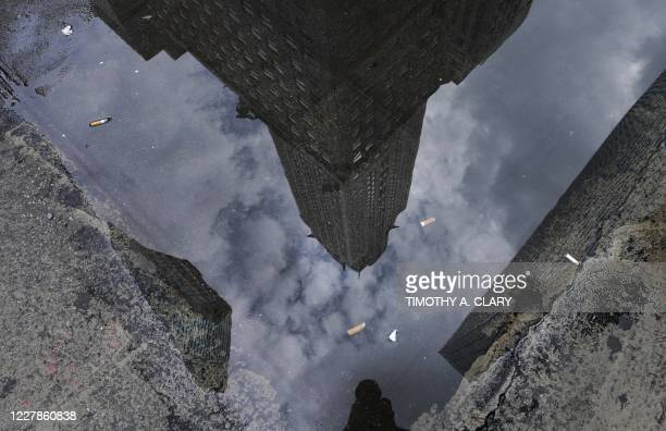 The Chrysler Building , Art Decostyle skyscraper in Midtown Manhattan, is reflected in a puddle of water on Lexington Avenue in New York July 31,...