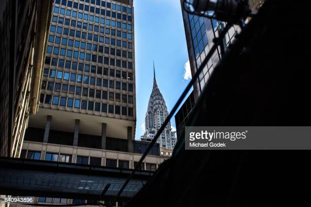 The Chrysler building peaking through a gap in the skyscrapers in Midtown Manhattan conveying the cramped crowded feeling of a city