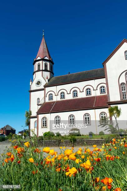 The Church of Sacred Heart of Jesus built in 1915 in Puerto Varas in the Lake District of Chile with California poppies in the foreground