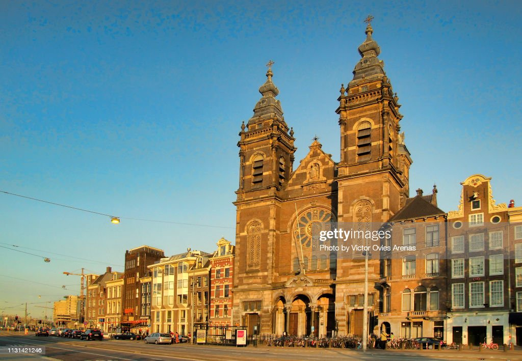 The church of Saint Nicholas on the Prins Hendrikkade quay near the Central Railway Station at sunset in Amsterdam, Netherlands : Foto de stock