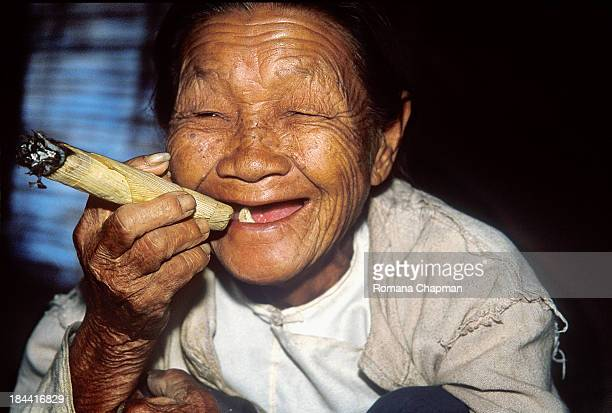 The cigar appears to be rolled with dried corn leaves. It takes so little to be happy. One tooth left in the mouth, a corn cigar and not much else....