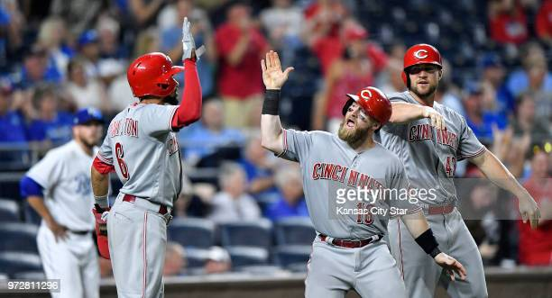 The Cincinnati Reds' Billy Hamilton Tucker Barnhart and Scott Schebler celebrate after scoring on a triple by Joey Votto in the 10th inning against...