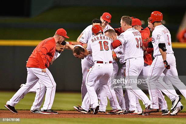 The Cincinnati Reds mob Scott Schebler of the Cincinnati Reds after Schebler hit a tworun double in the bottom of the ninth inning against the...