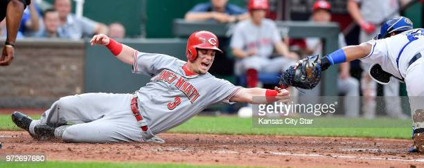 The Cincinnati Reds' Scooter Gennett left is tagged out by Kansas City Royals catcher Salvador Perez trying to score on a sacrifice fly by Jose...