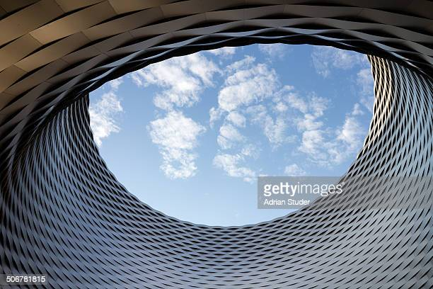 CONTENT] The circular opening in a modern building frames sky and clouds shaped like an eye due to perspective Messe Basel Switzerland