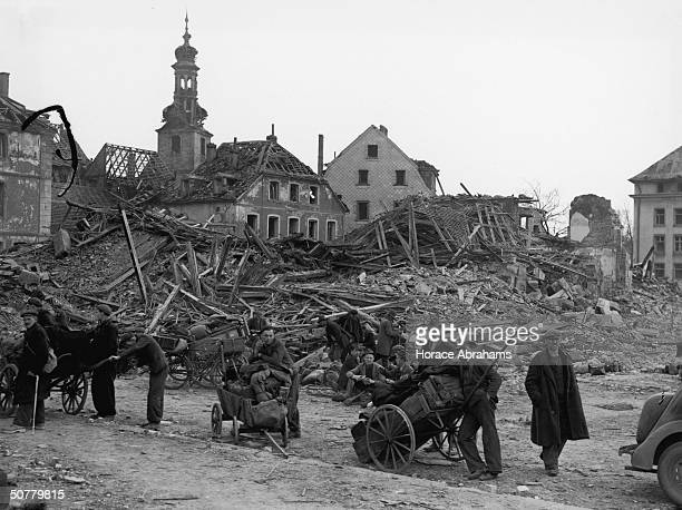 The citizens of Saarbrucken stand amidst the ruins of their city captured by the American 7th Army during World War II 22nd March 1945