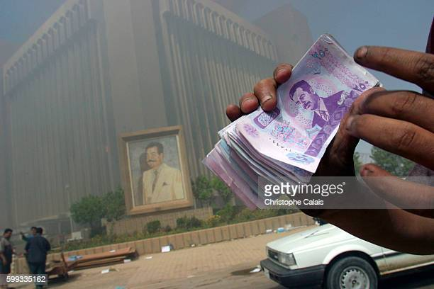 The city of Baghdad has been looted for 48 hours A young Baghdadi shows the money he found in the burning Ministry of Education