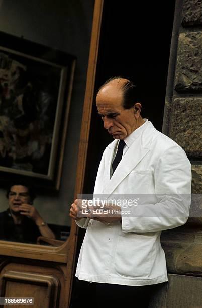 The City Of Florence Italy Florence juin 1967 Un serveur en veste blanche comptant sa monnaie adossé contre un mur à côté de la vitrine d'un...