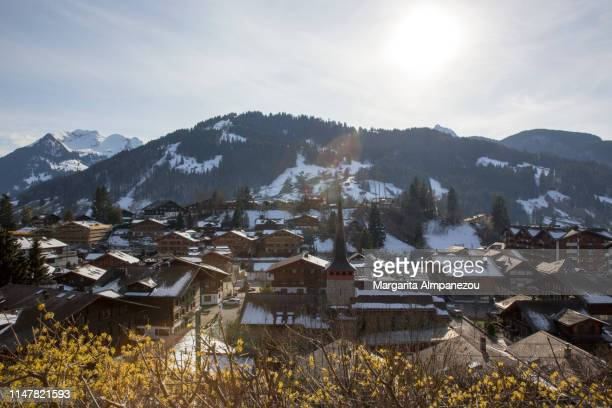 the city of gstaad with snow on the roofs and the surrounding mountains shot from above - グスタード ストックフォトと画像