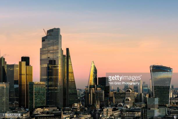 the city of london's financial district skyline at sunset - london england stock pictures, royalty-free photos & images