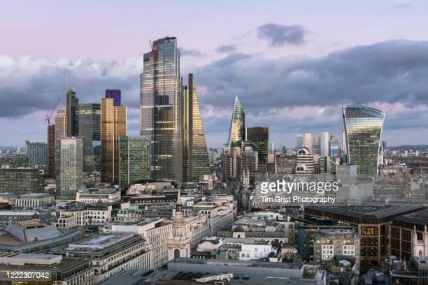 the city of london's illuminated financial district skyline - economic stimulus stock pictures, royalty-free photos & images