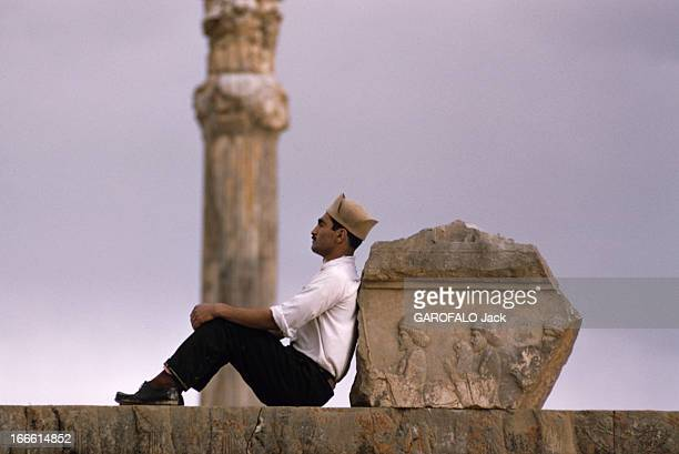The City Of Persepolis In Iran En Iran un homme en pantalon noir chemise blanche et portant un chapeau est assis contre un fragment de basrelief...