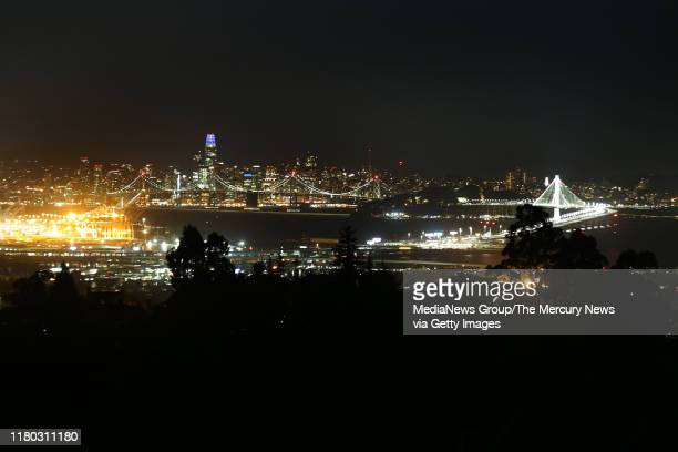 The city of San Francisco and the Bay Bridge are seen from the Oakland hills during the PG&E power outage in Oakland, Calif., on Thursday, Oct. 10,...