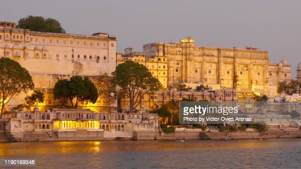 the city palace complex illuminated at twilight seen from lake pichola, udaipur, rajasthan, india - victor ovies fotografías e imágenes de stock