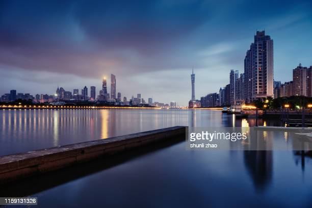 the city reflected on the sea - guangzhou stock-fotos und bilder