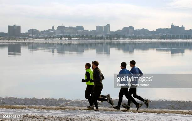 The city skyline is reflected in the relatively still waters of Back Cove while a group of runners strides along the shoreline trail on Friday
