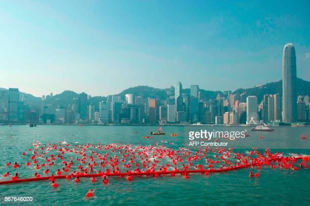 TOPSHOT The city skyline is seen in the background as competitors take part in the Harbour Race swimming event in Hong Kong's Victoria Harbour on...
