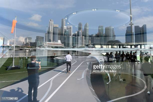 The city skyline with the prototype of Voloport takeoff and landing pad are reflected on a glass panel while visitors view the Volocopter unmanned...