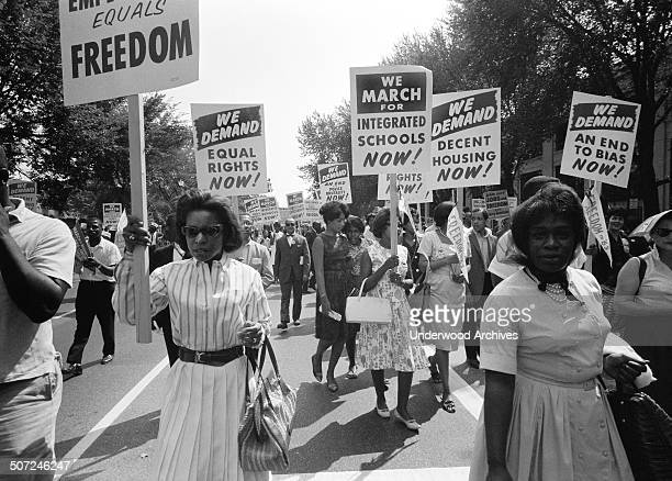 The civil rights march on Washington with a procession of African Americans carrying signs for equal rights and integrated schools Washington DC...