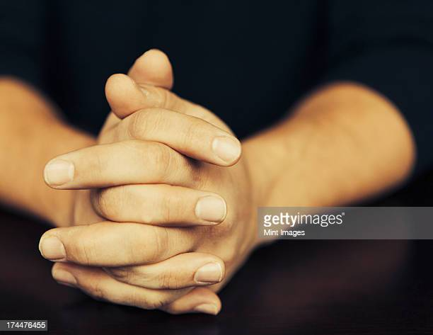 The clasped hands of a man wearing dark coloured clothes.