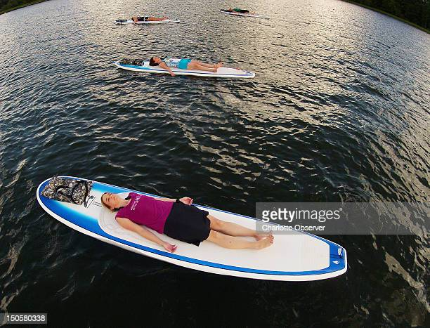 The classic corpse pose ends the session for Kim Shipes and the rest of the class July 30 on Jordan Lake in North Carolina It is a resting pose and...