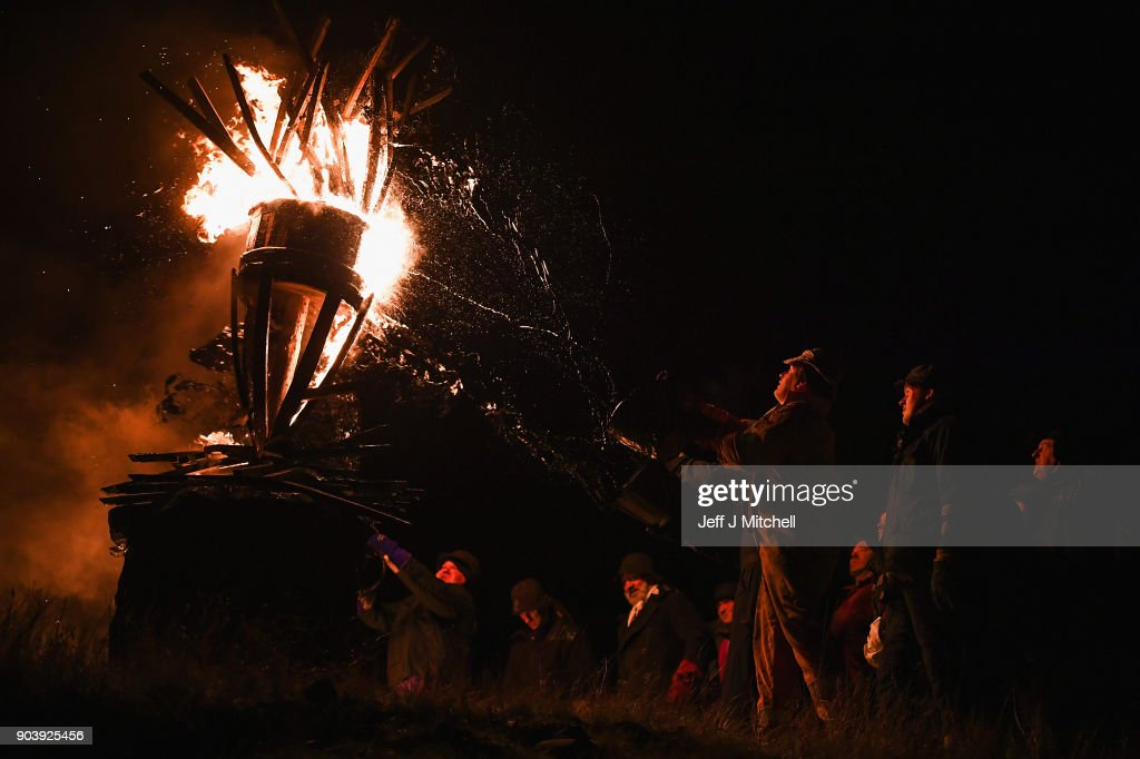 The Clavie, a burning barrel packed with tar soaked sticks fixed on the top of a pole, is surrounded by people at the Doorie Hill on January 11, 2018 in Burghead, Scotland. People welcome in the New Year with the fire ceremony which has ancient roots dating back to the 1750s, when the Julian calendar was reformed in Britain. It is believed to bring good luck for the coming year.