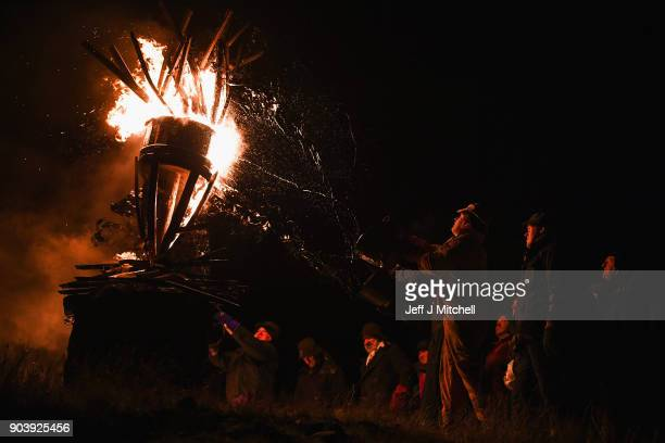 The Clavie a burning barrel packed with tar soaked sticks fixed on the top of a pole is surrounded by people at the Doorie Hill on January 11 2018 in...