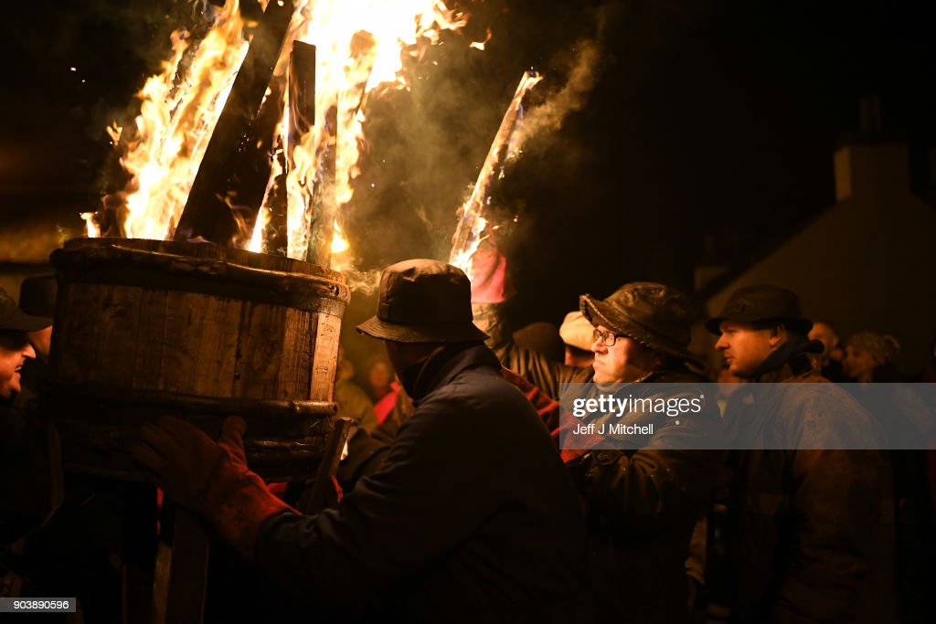 The Clavie King Dan Ralph and his squad hand out staves from the Clavie, which is a burning barrel packed with tar soaked sticks fixed on top of a pole, on January 11, 2018 in Burghead, Scotland. People welcome in the New Year with the fire ceremony which has ancient roots dating back to the 1750s, when the Julian calendar was reformed in Britain. It is believed to bring good luck for the coming year.
