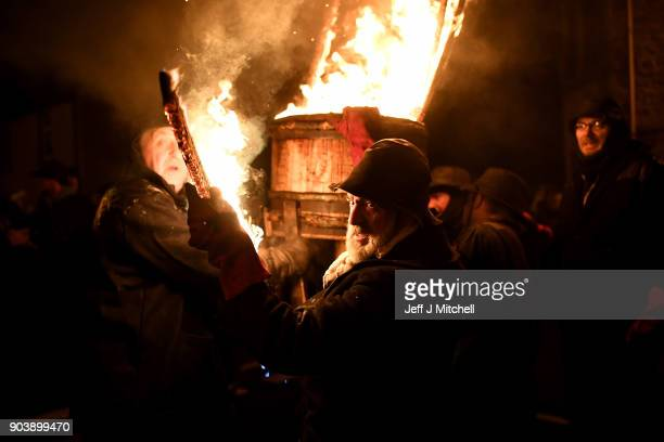 The Clavie King Dan Ralph and his squad hand out staves from the Clavie which is a burning barrel packed with tar soaked sticks fixed on top of a...