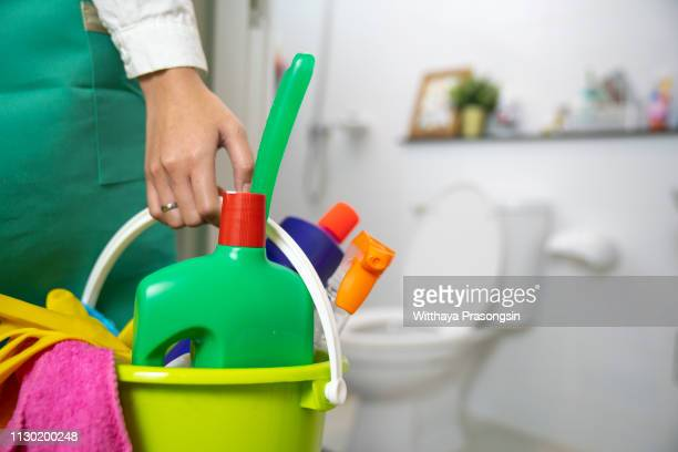the cleaning woman is standing in the bathroom holding a blue bucket full of chemicals and facilities for storing her hands. - limpio fotografías e imágenes de stock