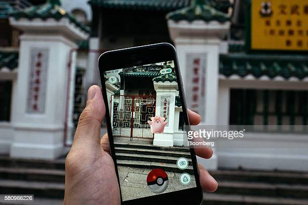 The Clefairy character of Nintendo Co's Pokemon Go augmentedreality game developed by Niantic Inc is seen in front of Man Mo Temple on a smartphone...