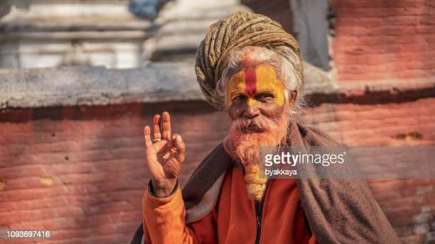 the cleric with a yellow beard in the temple pashupatinath - pashupatinath stock pictures, royalty-free photos & images
