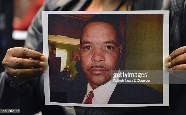 The Clerk of the Court holds up a photo of Reginald Daye 46 that was entered into evidence during the trial of Crystal Mangum Thursday Nov 14 2013 in...