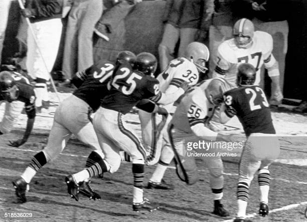 The Cleveland Browns' John Morrow makes a block on the Chicago Bears' Dave Whitsell and the Brown's running star Jim Brown is off for a 90 yard run...