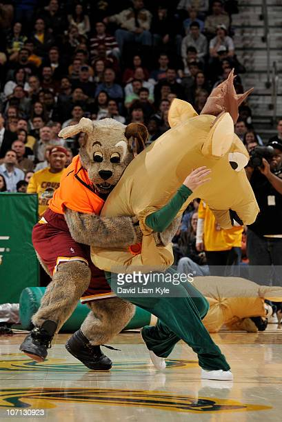 The Cleveland Cavaliers mascot Moondog tackles a bowling pin dressed as a Buck during a break in the action against the Milwaukee Bucks at The...