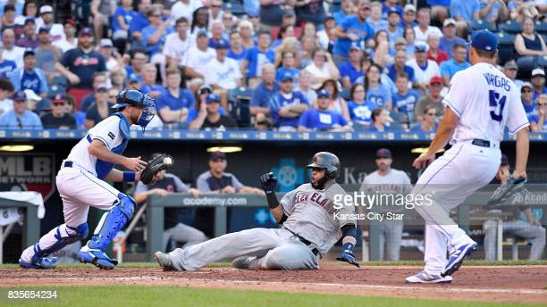 The Cleveland Indians' Carlos Santana slides safely at home ahead of the throw to Kansas City Royals catcher Drew Butera left on a tworun single by...
