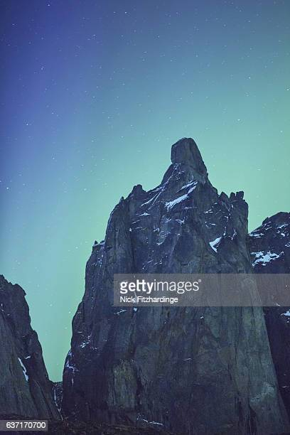the cliff face of mount monolith backlit by aurora borealis glow, tombstone territorial park, yukon territory, canada - rock wall stock pictures, royalty-free photos & images