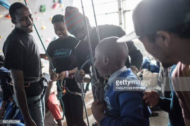The climbing gym staff congratulate a student as he finishes rope climbing during a weeklong free climbing training for visually impaired and blind...