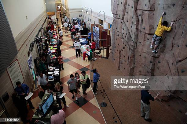 The climbing wall makes a dramatic backdrop as booths line the hallway at for the Sports and Healthy Fitness event at Claude Moore Recreation Center...