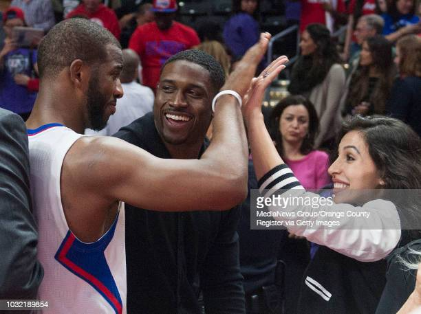 The Clippers' Chris Paul highfives Lilit Avagyan next to her husband Reggie Bush after the Clippers' 119115 victory over the San Antonio Spurs at...