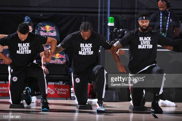 The LA Clippers kneel during the National Anthem before the game against the Brooklyn Nets on August 9 2020 at AdventHealth Arena in Orlando Florida...