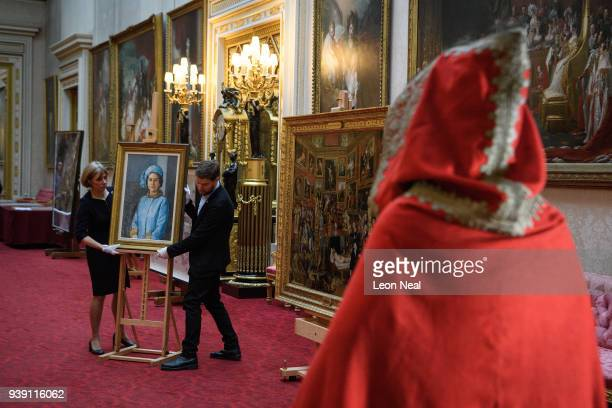 The cloak of Napoleon Bonaparte is seen as members of the Royal Collection Trust staff pose with the 'HM The Queen 197273' by Michael Noakes to...