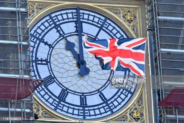TOPSHOT The clock face of Elizabeth Tower known after the bell Big Ben shows the hands at eleven o'clock as a Union Flag flies in front of it in...