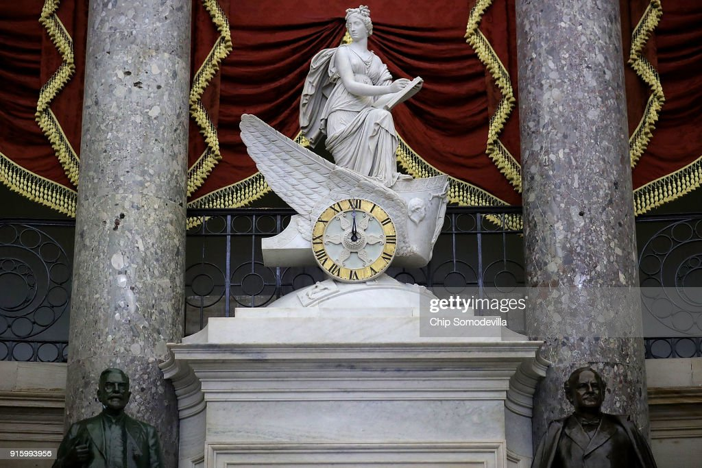 The clock in the National Statuary Hall shows midnight at the U.S. Capitol February 9, 2018 in Washington, DC. Despite attempts by Republicans and Democrats to strike a deal to avoid a government shutdown, Sen. Rand Paul (R-KY) forced the Senate to delay a vote and force the federal government into a partial shutdown.